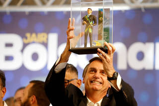 FILE PHOTO: Federal deputy Jair Bolsonaro, a pre-candidate for Brazil's presidential elections, shows a doll of himself during a rally in Curitiba