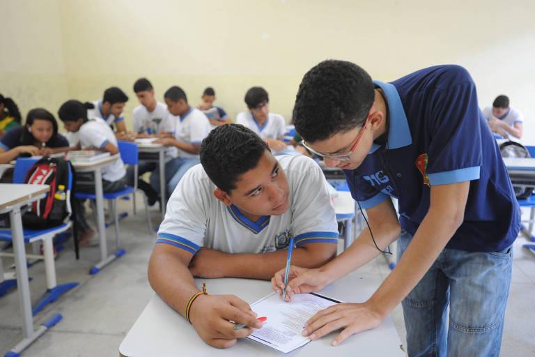 Foto mostra um aluno em pé ensinando colega, sentado, em sala de aula do ensino médio em escola de Jaboatão dos Guararapes, em PE