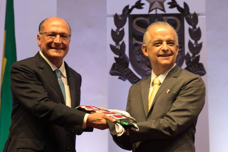 O ex-governador de São Paulo Geraldo Alckmin transmite o cargo para Márcio França. Alckmin e França seguram juntos a bandeira do estado, dobrada.