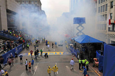 Medical workers aid injured people at the 2013 Boston Marathon following an explosion in Boston, Monday, April 15, 2013. Two explosions shattered the euphoria of the Boston Marathon finish line on Monday, sending authorities out on the course to carry off the injured while the stragglers were rerouted away from the smoking site of the blasts. (AP Photo/The Boston Globe, David L Ryan)   ORG XMIT: MABOD804