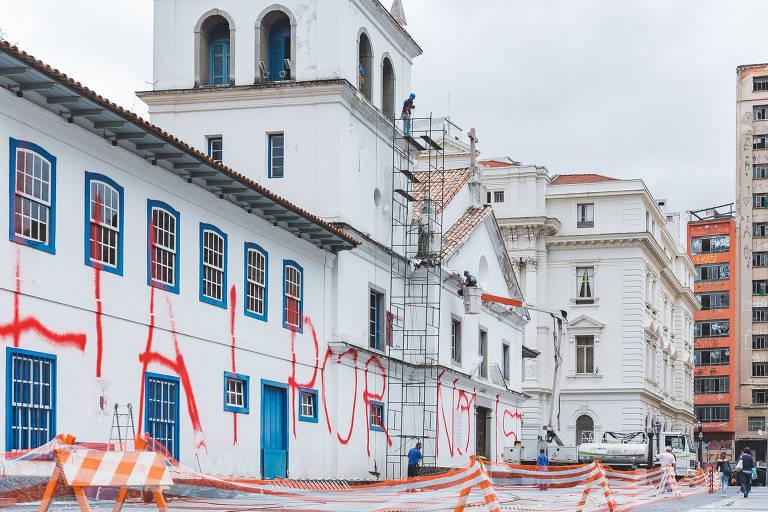"""Voluntários iniciam limpeza da fachada do Pateo do Collégio pichado com a frase """"Olhai por nois"""""""