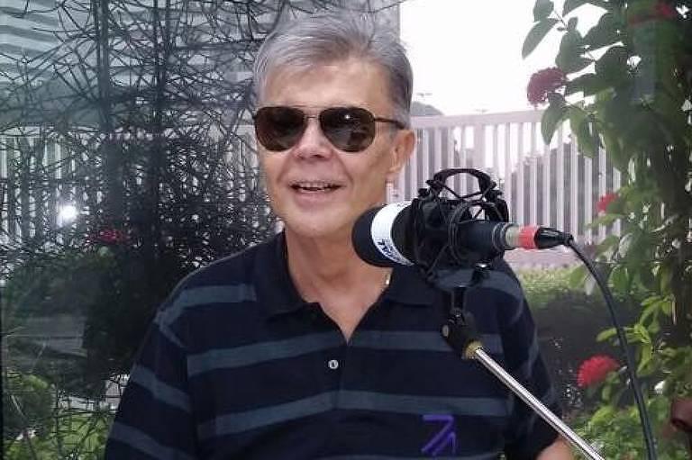 O radialista sentado em frente ao microfone da rádio