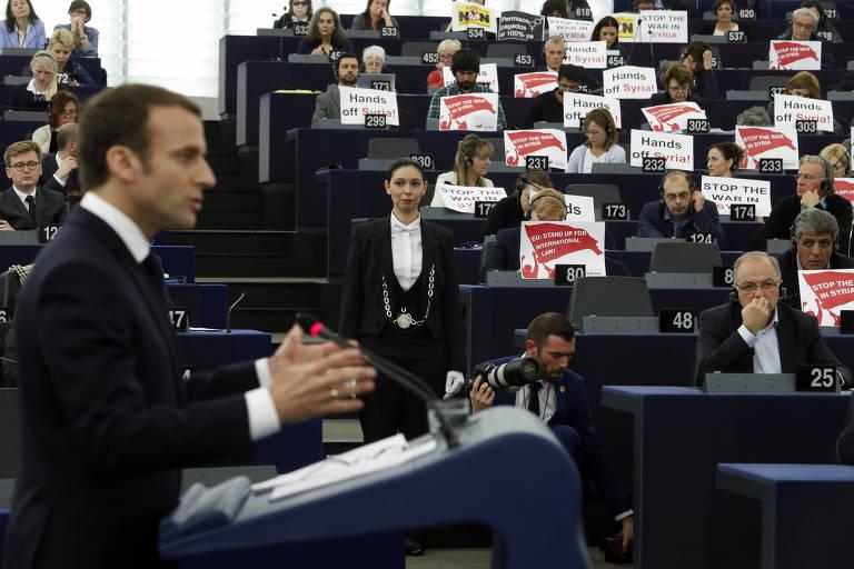 Enquanto Emmanuel Macron discursa no Parlamento Europeu, deputados erguem cartazes contra a ação na Síria