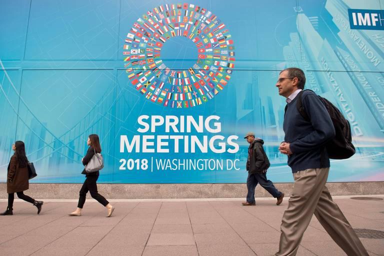 Pessoas caminham perto de placa sobre encontro do FMI em Washington