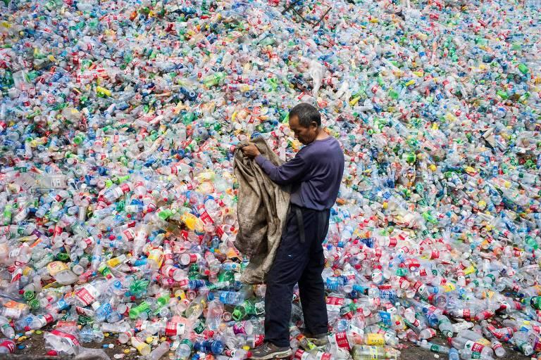 Trabalhador chinês organiza garrafas plásticas para reciclagem