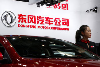 FILE PHOTO - A hostess poses next to Dongfeng Motor Corp A9 sedan at the Auto China 2016 auto show in Beijing