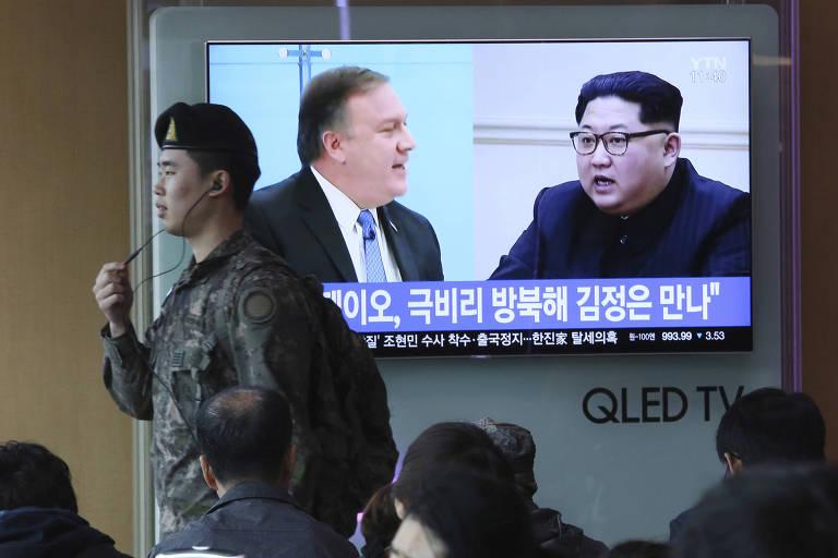 Soldado passa em frente a uma televisão em Seul que exibe a imagem do ditador norte-coreano Kim Jong-un (dir.) e do diretor da CIA, Mike Pompeo