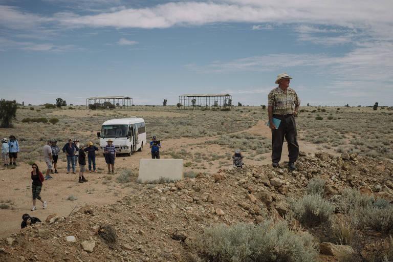 Van branca em campo de terra, com vegetação rasteira. Grupo de pessoas ao redor da van e homem afastado, em primeiro plano, com chapéu