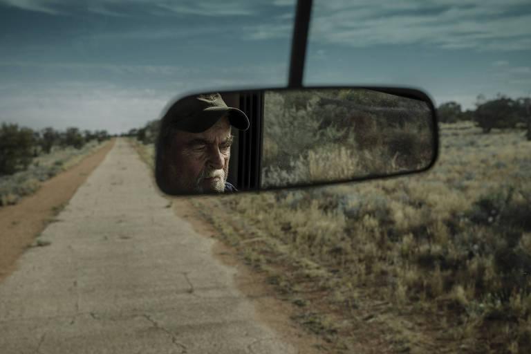 Estrada de terra, com vegetação rasteira, vista de um carro. Vê-se um homem por um espelho retrovisor
