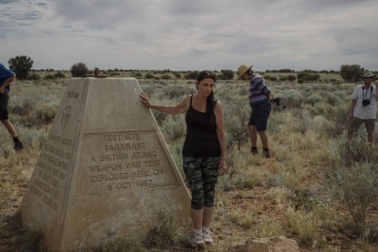 Pessoas num campo com grama, céu nublado., Na frente, há uma pirâmide de cimento no qual uma mulher se apoia