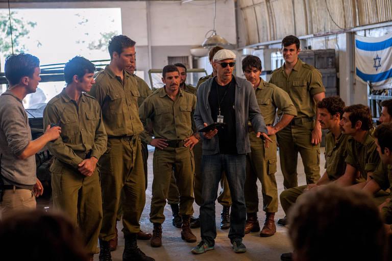 """José Padilha (de boné branco) dirige grupo de atores que encarnam militares em """"7 Dias em Entebbe"""""""