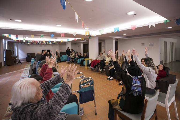 Idosos se exercitam em residência para terceira idade em São Paulo. Idosos sentados levantam os braços para se exercitar