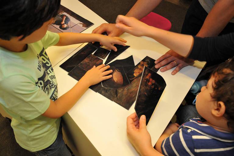 Crianças montam quebra-cabeça com imagem de obra do acervo da Pinacoteca