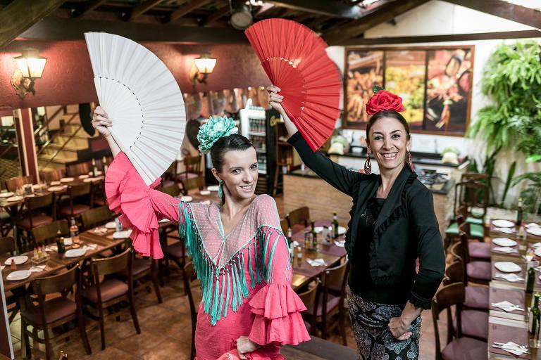 Duas dançarinas de flamenco seguram leques nas mãos