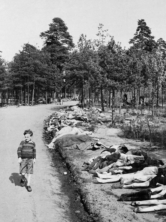 Um garoto caminha por uma pilha de corpos no campo de concentração de Bergen-Belsen, na Alemanha