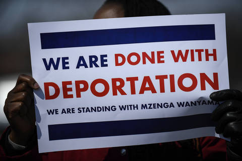 A demonstrator held up a sign in support of Augsburg Professor Mzenga Wanyama Thursday, April 5, 2018, outside of the Immigration and Customs Enforcement Headquarters in St. Paul, Minn. Wanyama and his wife Mary returned to Immigration and Customs Enforcement headquarters Thursday,  for another check-in to discuss the agency's plan to deport them. Wanyama emerged to a crowd of supporters to tell them that he and his wife have been given 90 days to leave the country.  (Aaron Lavinsky/Star Tribune via AP) ORG XMIT: MNMIT104