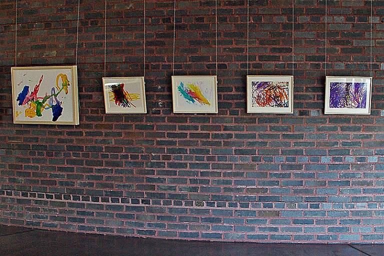 quadros coloridos na parede de tijolos