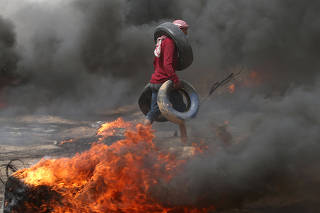 Demonstrator carries tires during clashes with Israeli troops at a protest where Palestinians demand the right to return to their homeland, at the Israel-Gaza border in the southern Gaza Strip