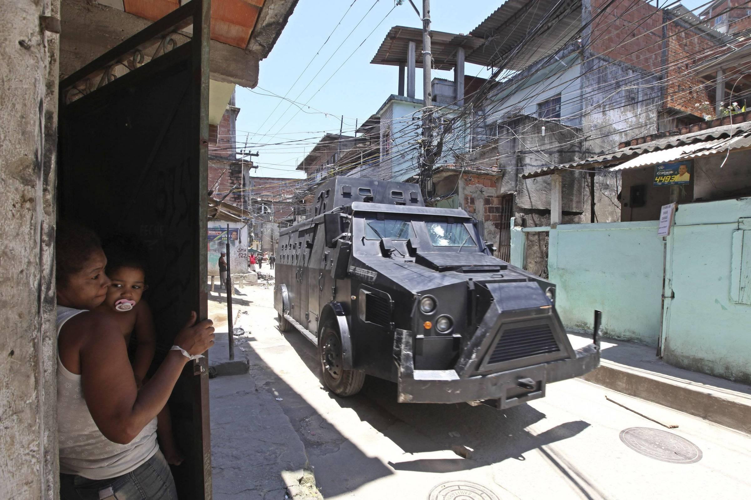 Caveirão usado pela PM do Rio para operações em favelas; na imagem, moradora do Complexo do Alemão segura bebê e se protege durante passagem de veículo blindado - Andre Penner - 28.nov.2010/Associated Press