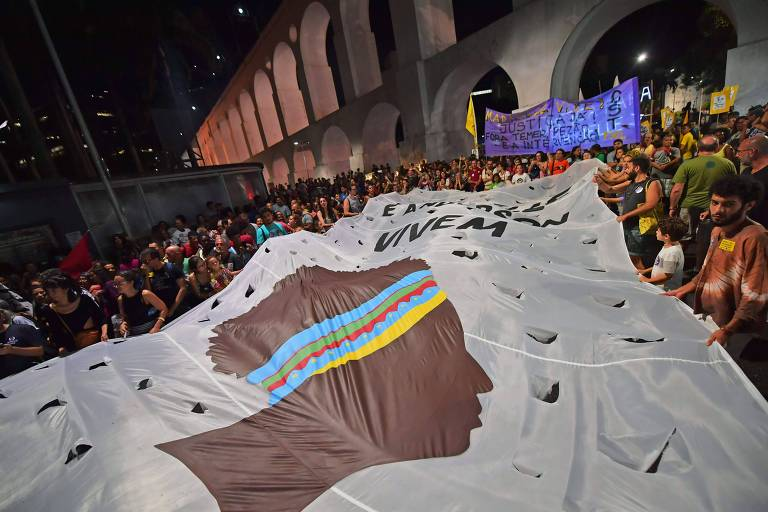 Manifestantes exibem bandeira gigante com o desenho de uma mulher negra; ao fundo, os arcos da Lapa