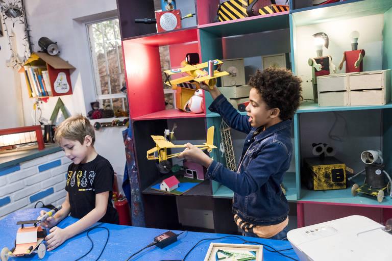 As crianças Rafael (à esq.) e Luca brincam com miniaviões amarelos durante oficina com pais de filhos na Casa das Ideias, em SP