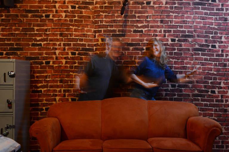 Henrique Sitchin, 53, e Karina Prall, 49, fundadores do Escape Junior, em frente a uma parede de tijolos, ligeiramente desfocados