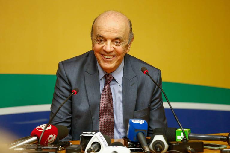 José Serra cercado por microfones da imprensa
