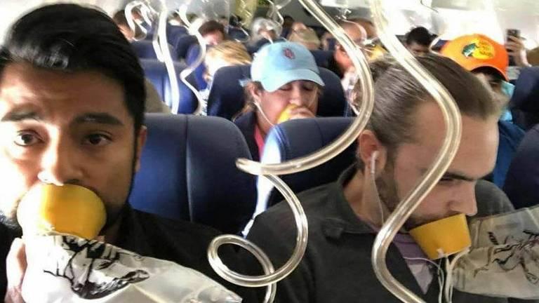 A foto mostra uma cabine da classe econômica de um avião. Todos usam máscara de oxigênio, mas de maneira incorreta: elas cobrem apenas a boca e não o nariz