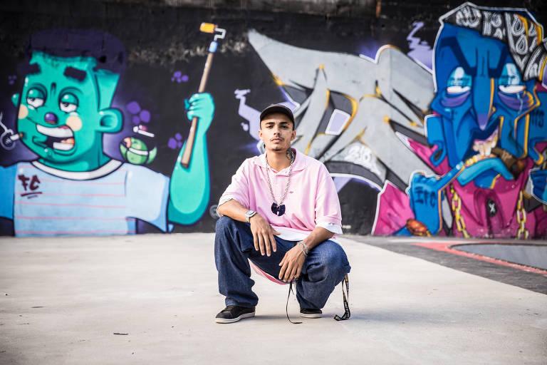 O grafiteiro Deley é retratado em frente aos grafites feito por ele um amigo no muro da galeria V. Garage
