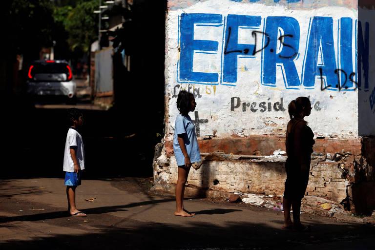 Pessoas observam muro pintado com nome do candidato à Presidência do Paraguai Efraín Alegre, de oposição, em Assunção