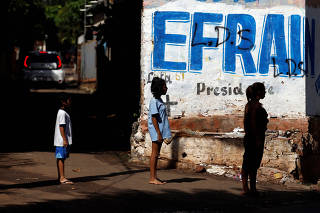 People stand in front of a wall painted with the name of Presidential candidate of the GANAR coalition Efrain Alegre ahead of the April 22 elections, in Asuncion
