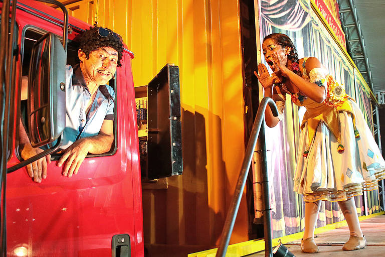 Foto mostra o caminhão vermelho e amarelo do projeto itinerante Teatro a Bordo; da boleia, sai um ator com ares de palhaço e, ao lado, fazendo gesto como se gritasse chamando alguém, uma atriz, também com roupas de aspecto circense