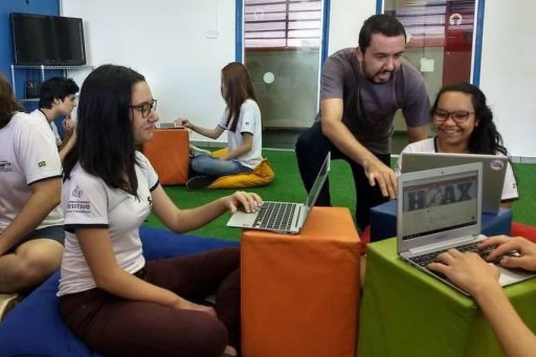Professor fala com alunos em sala de aula