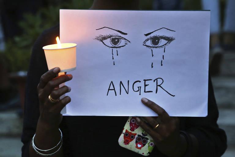 """Mulher segura cartaz com a palavra """"raiva"""" em protesto contra violência a mulheres, que cresce na Índia"""