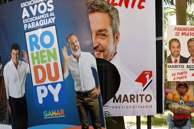 Vendedor passa por pôsteres de dois candidatos à Presidência paraguaia, Efraín Alegre e Mario Abdo Benítez, em Assunção