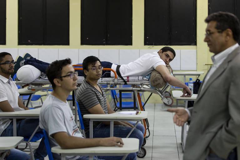 Imagem mostra estudante deitado de bruços sobre maca dentro de sala de aula. Outros estudantes estão sentados em cadeiras e um professor fala para todos
