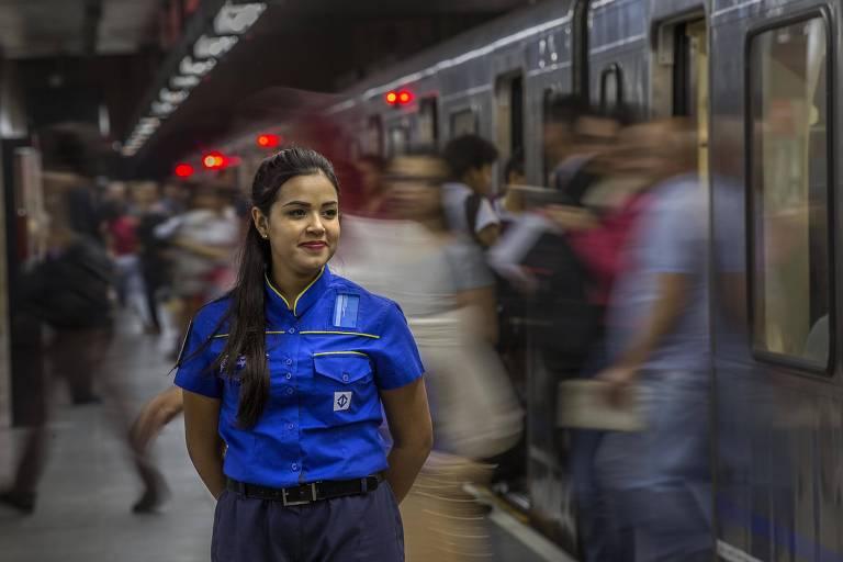 Mulher usa uniforme azul em estação de metrô