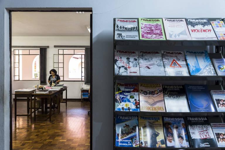 Estante com revistas dispostas lado a lado; ao fundo, mulher mexe em papeis em mesa