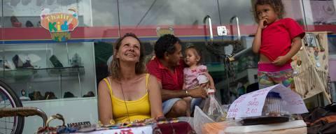 A Brazilian woman sells handcraft bijouteries displayig a sign reading