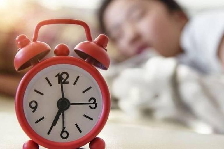 Despertador vermelho, com pessoa dormindo ao fundo
