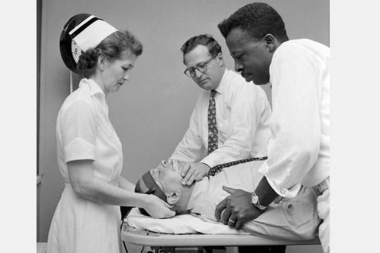 Foto em preto e branco dois homens e uma enfermeira segurando um paciente deitado para eletrochoque