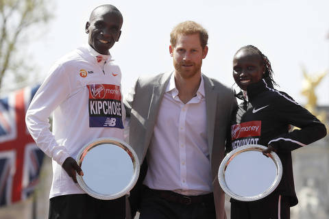Britain's Prince Harry, centre, poses with Eliud Kipchoge of Kenya, left, and Vivian Cheruiyot of Kenya, right, the winners of the men's and women's races in the London Marathon in London, Sunday, April 22, 2018. (AP Photo/Kirsty Wigglesworth) ORG XMIT: LKW106