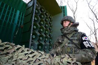 South Korean soldiers draw down a cover from loudspeakers just south of the demilitarized zone separating the two Koreas in Yeoncheon