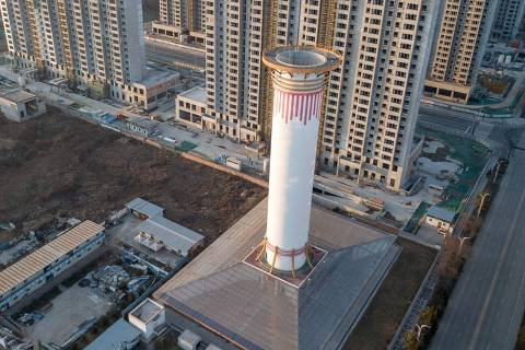 This picture taken on February 13, 2018 shows an aerial view of an air purification tower in Xian. China has a big air pollution problem. So, it is turning to an equally big solution: giant air purifiers. The massive structure on the outskirts of the Xian, the capital of the northern province of Shaanxi, looks like a chimney. But instead of pumping out billows of black smoke, like the towers rising from factories around the region, it blasts out the kind of clean air typically only find in the world's most pristine environments. / AFP PHOTO / Fred DUFOUR / TO GO WITH China-pollution ORG XMIT: FD002542