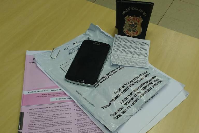 Foto mostra celular e provas do enem em mesa