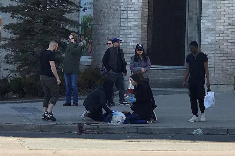 Vítima ferida é auxiliada por pedestres após ser atingida por uma van que atropelou diversas pessoas em uma avenida de grande movimento em Toronto, no Canadá