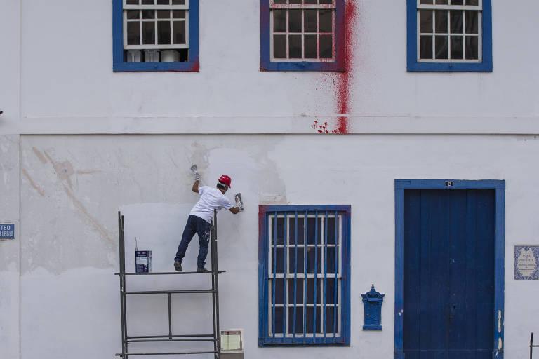Voluntário trabalha na restauração da fachada do Pateo do Collegio, no centro de SP, após pichação