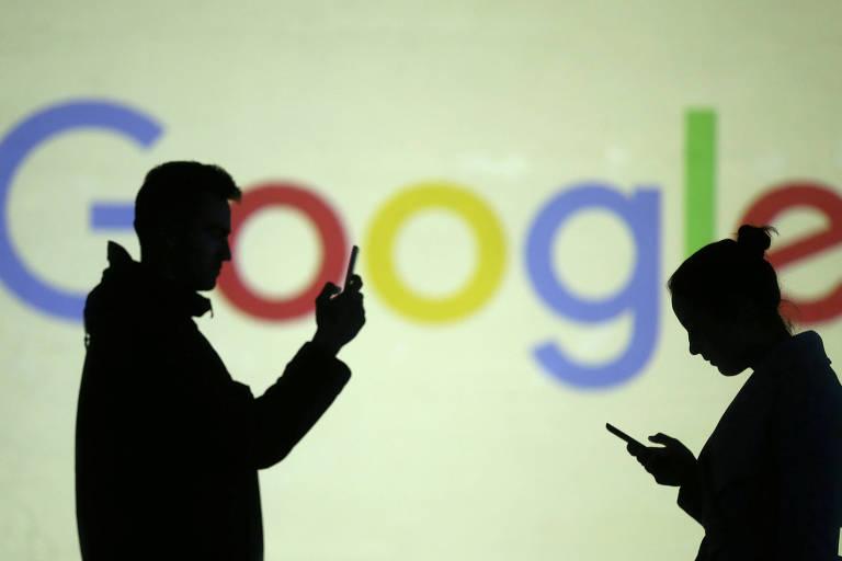 Duas pessoas acessam a internet pelo celular em frente ao logotipo do Google