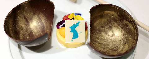 This undated picture released by the South Korean presidential Blue House on April 24, 2018 shows a mango mousse cake decorated with a garnish in the shape of a unified Korean peninsula, which will be served at the dinner of the upcoming inter-Korean summit.  The cake is in a wooden bowl, a symbol of Cold War confrontation, which will be broken by a hammer to symbolize the start of reconciliation. Symbolism will be the main course of a banquet at the upcoming inter-Korean summit, Seoul revealed on April 24, with a menu featuring Pyongyang's signature dish and food from the home towns of the South's leaders at previous meetings. / AFP PHOTO / The Blue House AND AFP PHOTO / handout / RESTRICTED TO EDITORIAL USE - MANDATORY CREDIT