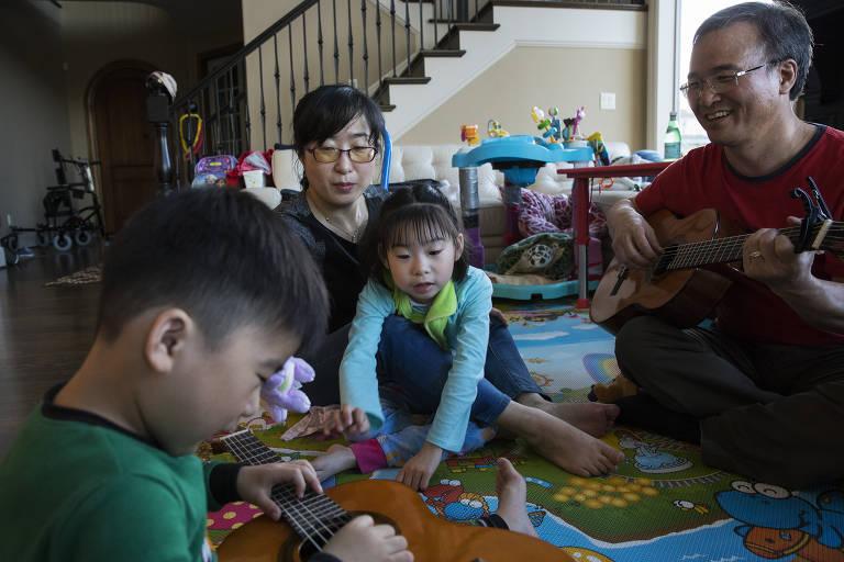 Mãe e pai, com os dois filhos, brincam em casa